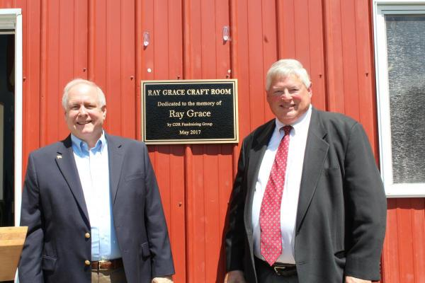 Christian Appalachian Project's President and CEO Guy Adams (left) and Geoff Peters, CEO of Moore DM Group, dedicate the Ray Grace Craft Room at Camp AJ.