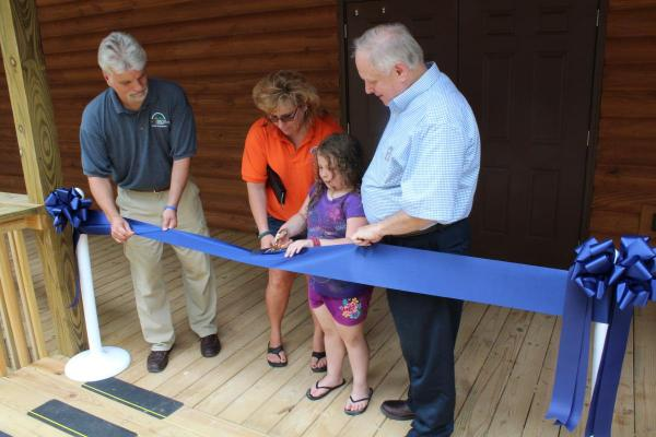 (From left) Owen Wright, Pat Griffith, and Guy Adams assist second-year camper Natalee with cutting the ribbon at the dedication of Bradford Hall, the new girls' dormitory at Camp Shawnee.