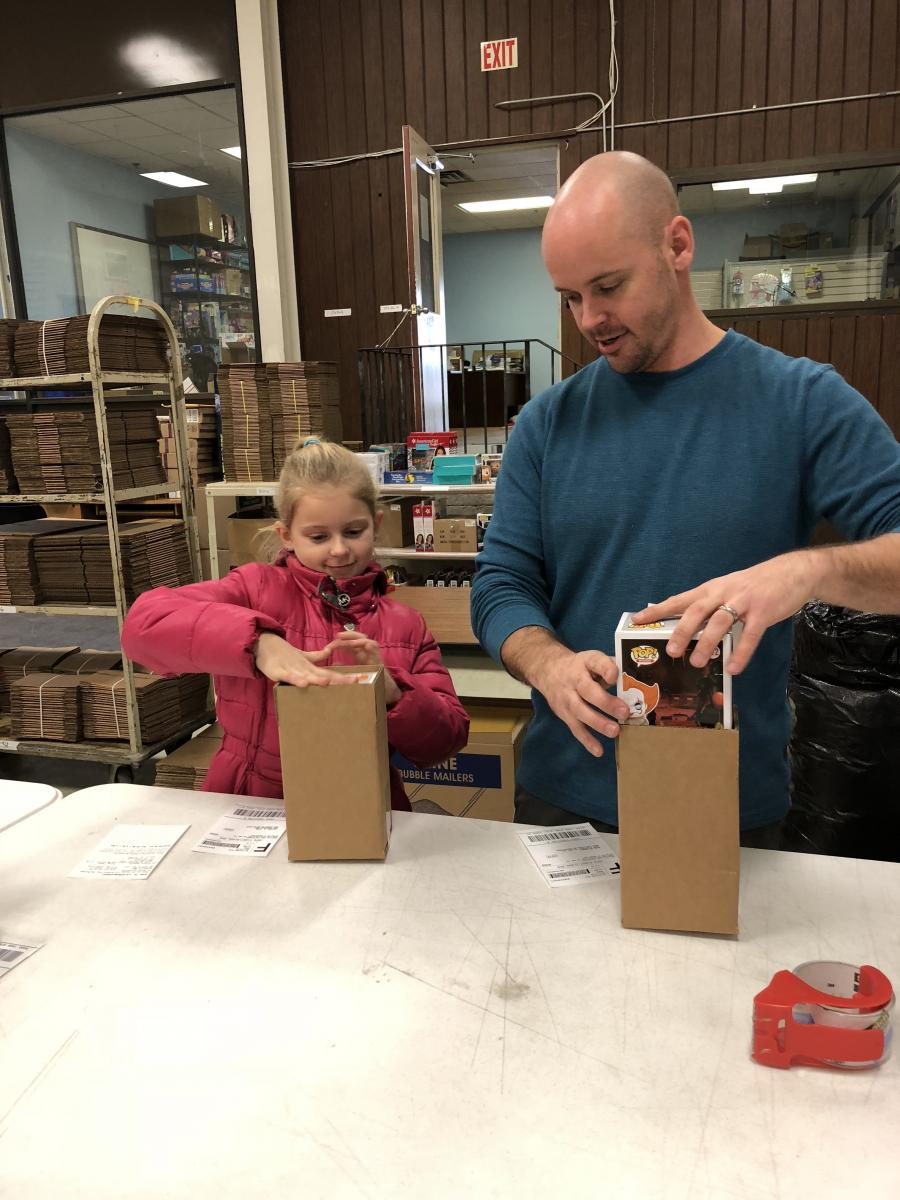 Clay Hensley, joined by his daughter Lexi, processes Christmas orders at Happen Stock Toys on Palumbo Drive.