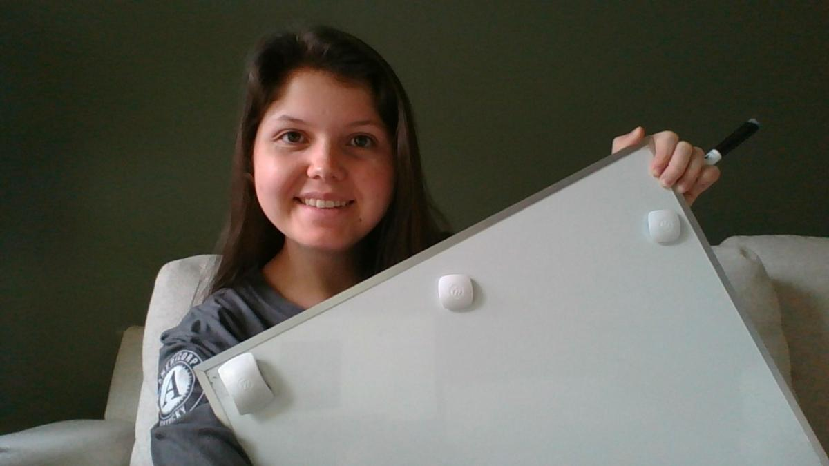 Kathryn holding a whiteboard used to virtually tutor students