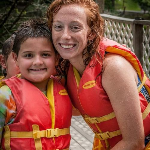 A camper and camp counselor wearing life jackets, smiling.