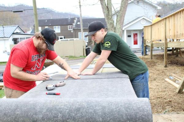 Antone Clohessy (left) and Caden Klatt (right) with YouthGo in Neenah, Wis. cut tar paper to apply to a handicap accessible ramp to prevent falls.