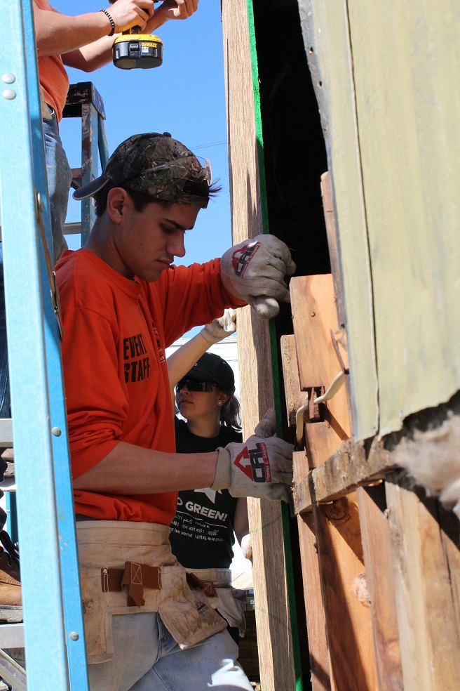 IMAGE: Matthew Chebowski helps replace siding and a window for a mother who just purchased her first home.